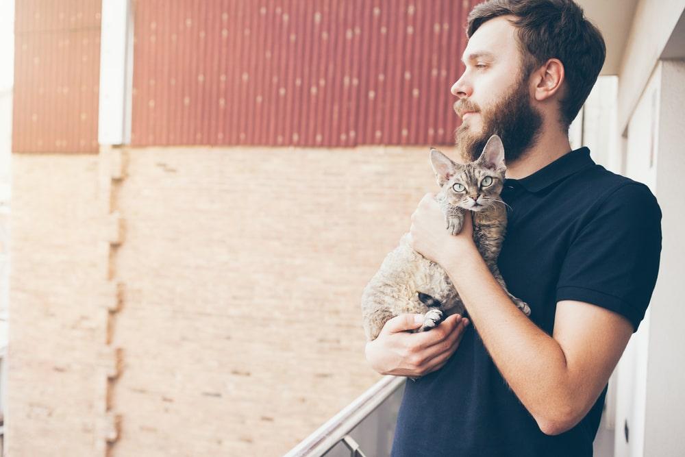 Mann trägt Katze auf dem Arm
