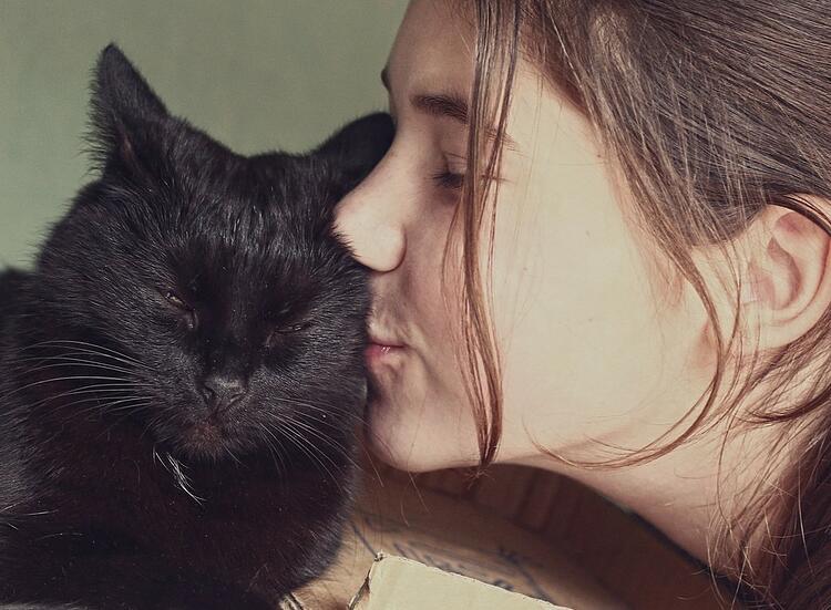 une jeune fille embrasse un chat noir